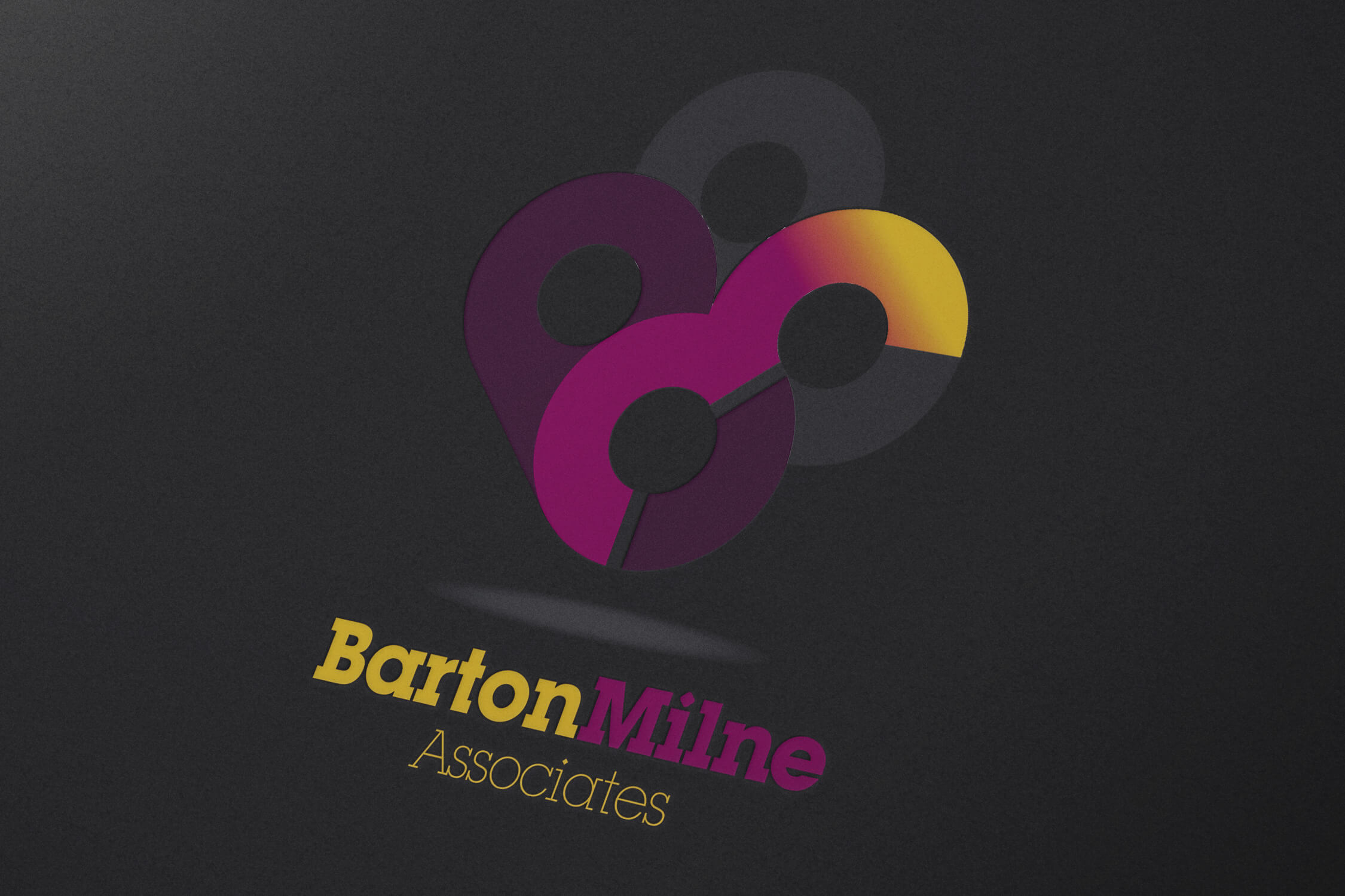 The Barton Milne Associates logo on dark paper background