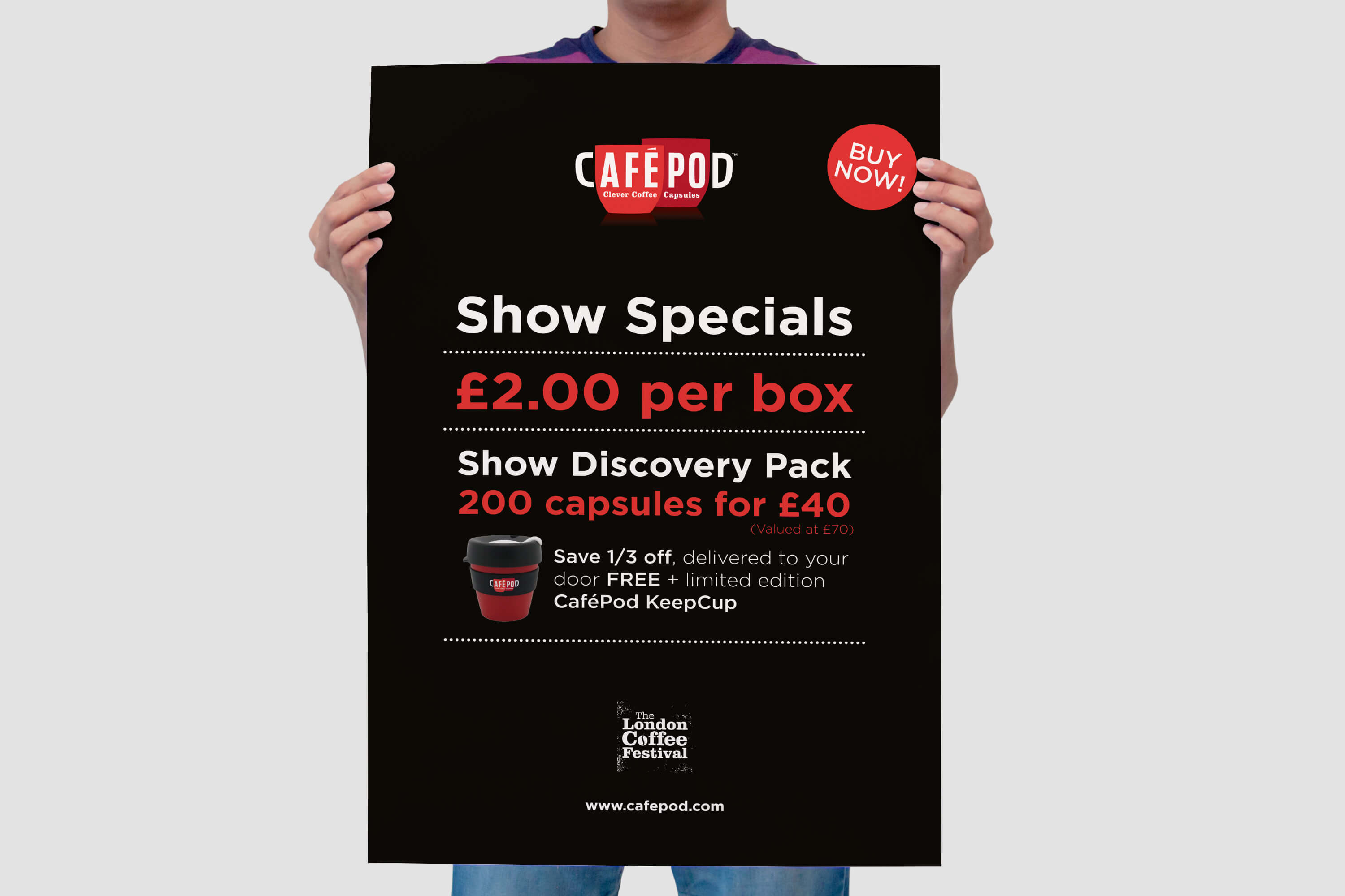 Person holding a printed CaféPod table talker poster for a trade show