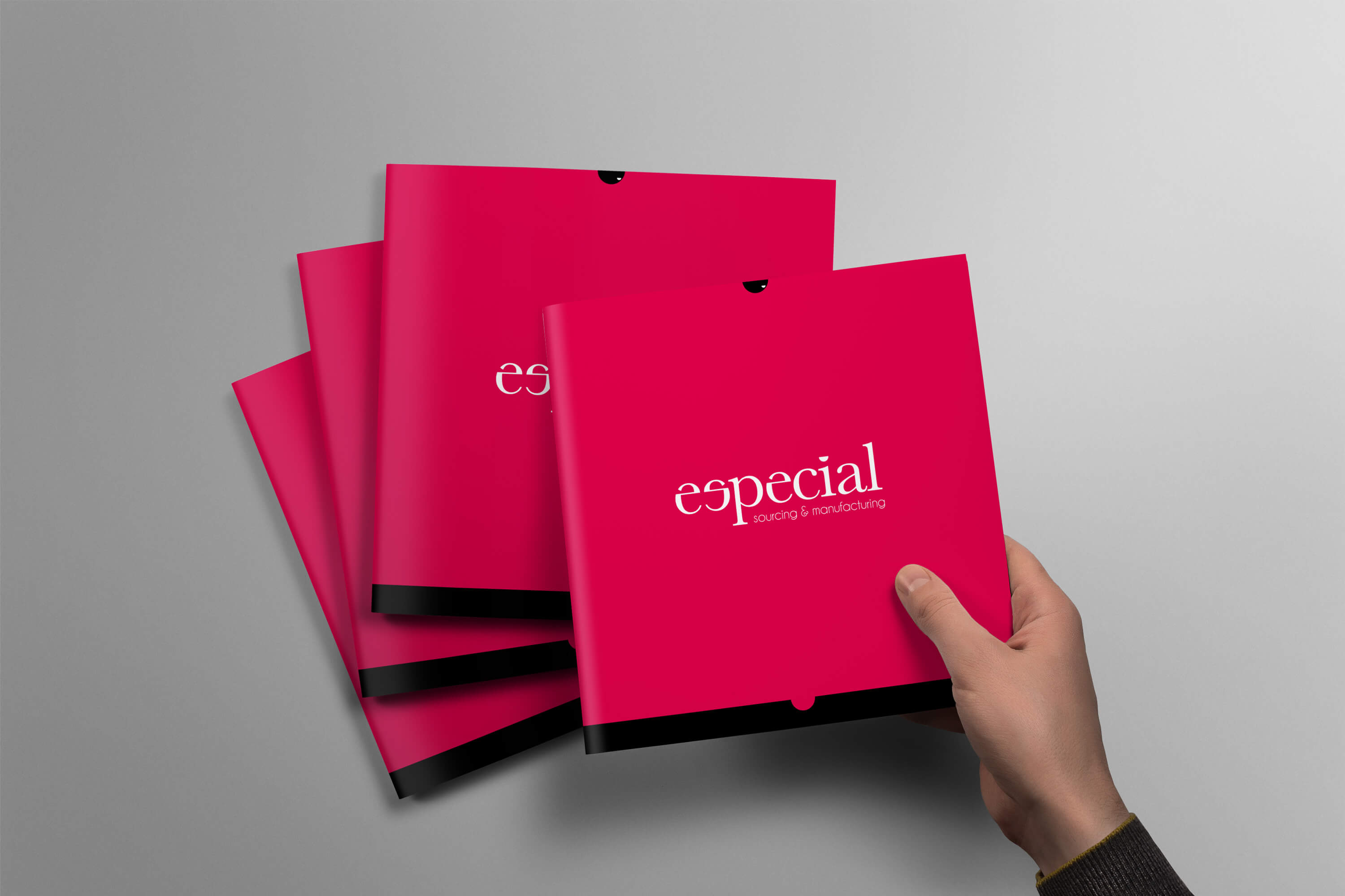 Person taking a copy of the Especial Sourcing and Manufacturing brochure from the top of a pile of brochures