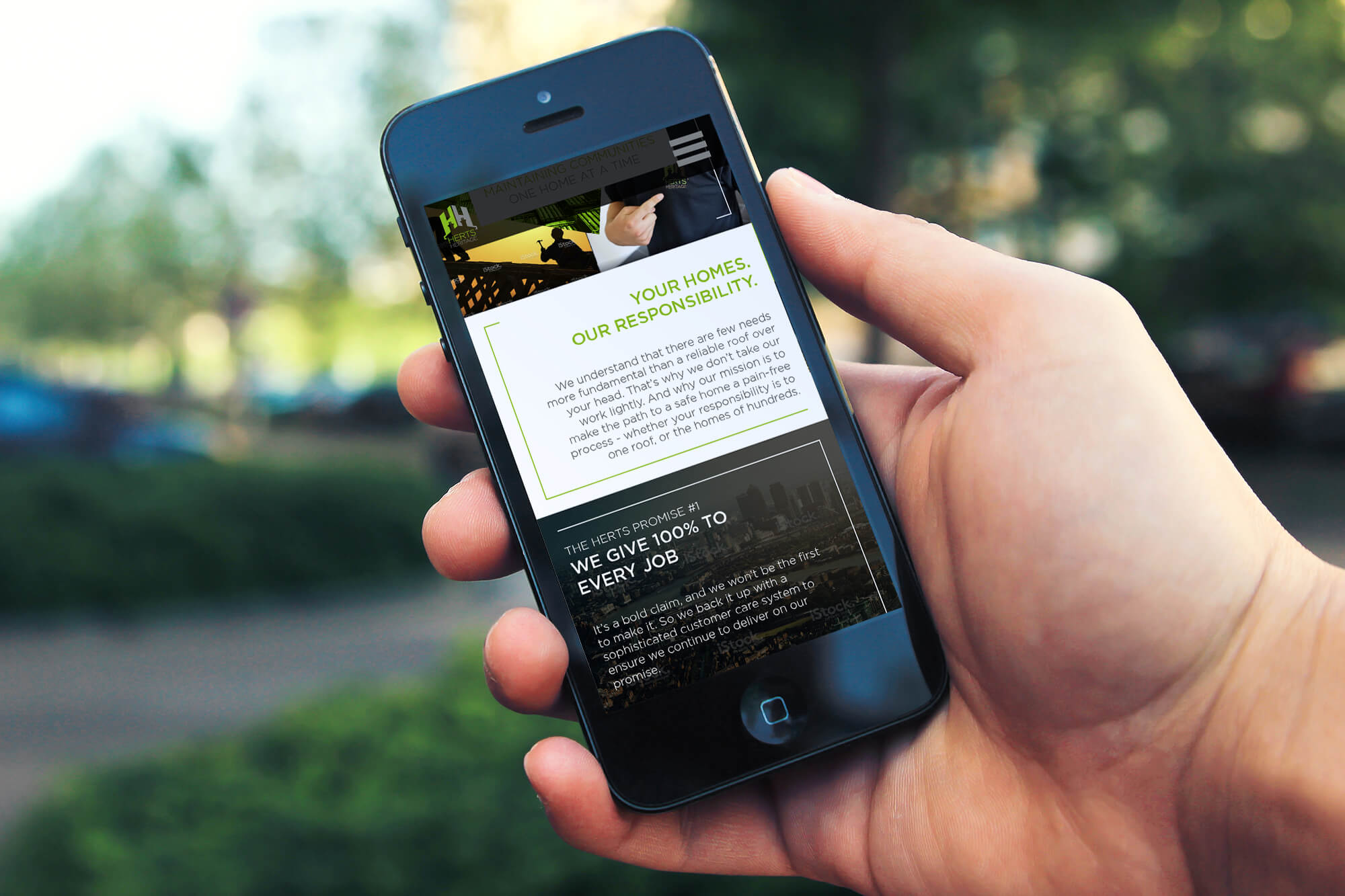 Close up of person holding an iPhone displaying the Herts Heritage website rebrand design
