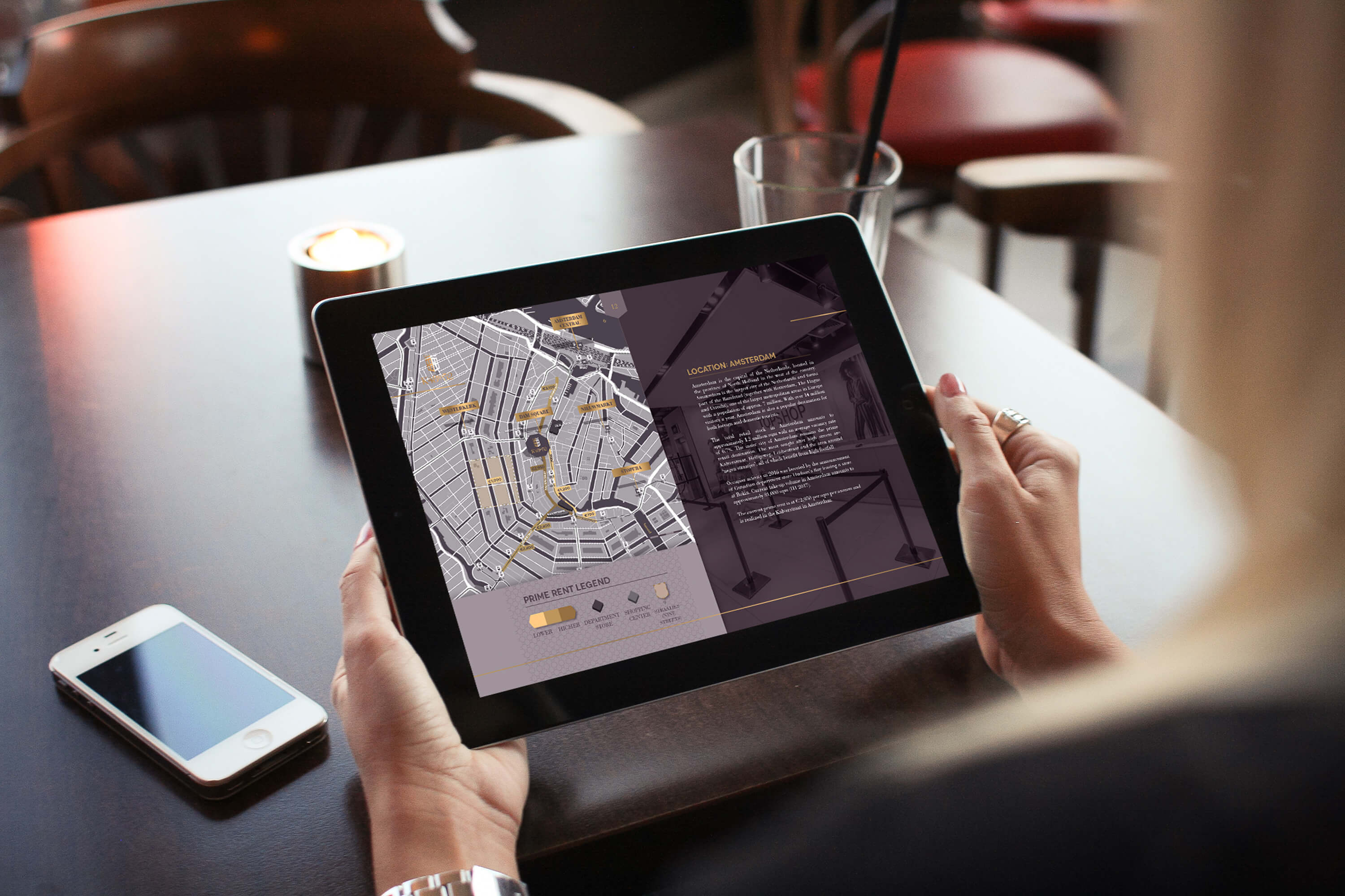 A woman holding a tablet showing the bespoke map and internal page within the JLL K48to52 investment memorandum design