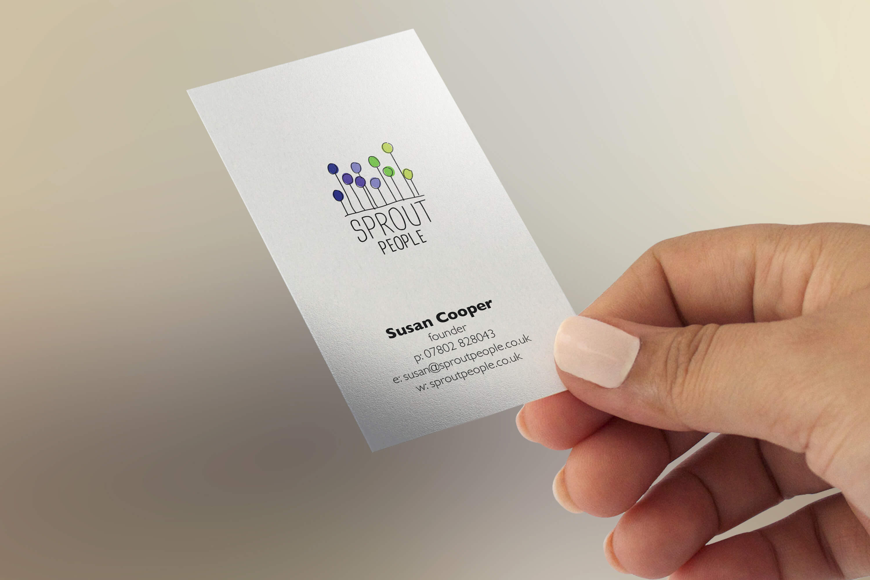 A woman's hand holding a copy of the Sprout People business card design