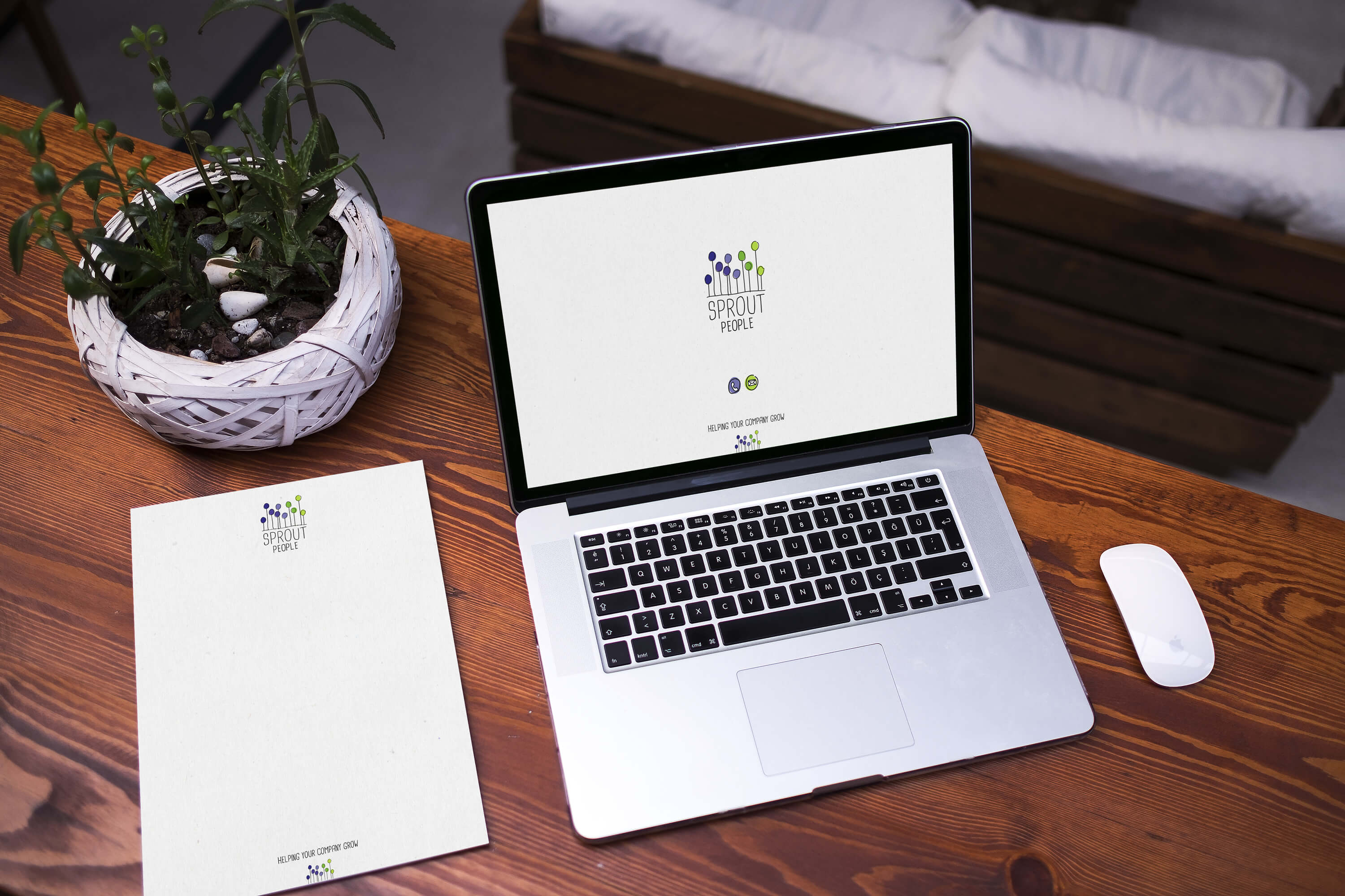 A laptop and letterhead on a desk showing the Sprout People brand identity